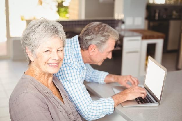 Porträt der älteren frau mit dem ehemann, der laptop im hintergrund verwendet