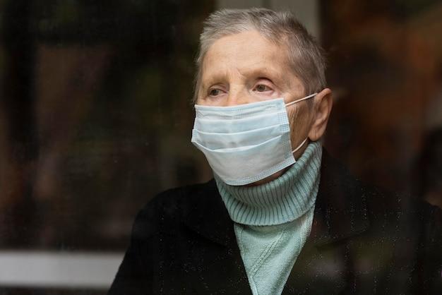 Porträt der älteren frau mit medizinischer maske