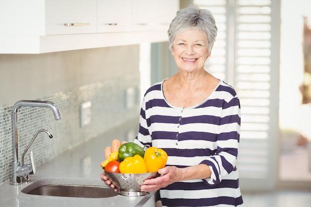 Porträt der älteren frau sieb mit gemüse halten