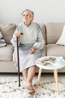Porträt der älteren großmutter, die auf sofa sitzt