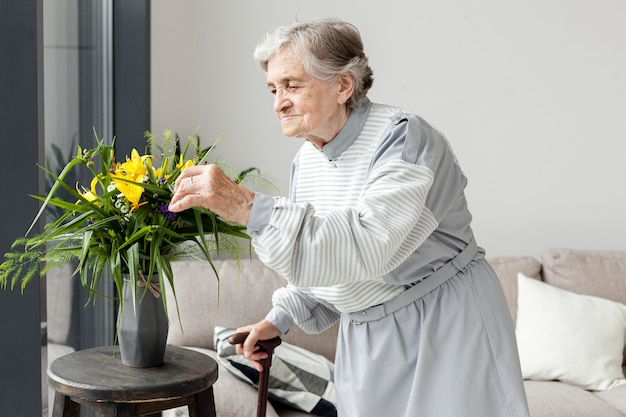 Porträt der älteren großmutter, die blumen berührt