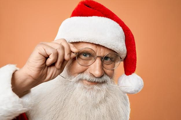 Porträt der älteren netten santa claus, die hand auf gläsern hält