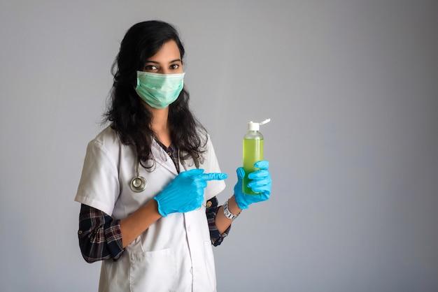 Porträt der ärztin, die eine flasche desinfizierendes gel für die händereinigung zeigt.