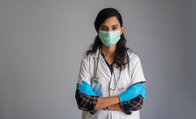 Porträt der ärztin, die eine schutzmaske und handschuhe mit einem stethoskop trägt. welt-epidemie des coronavirus-konzepts.