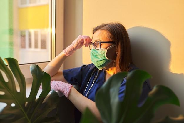 Porträt der ärztin, die medizinische gesichtsmaske zur vorbeugung gegen virusinfektion verwendet,