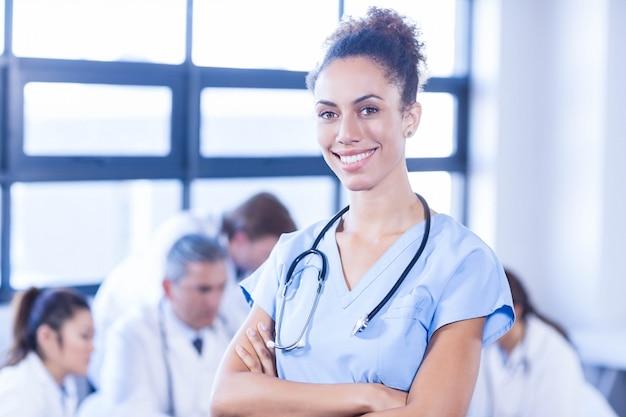 Porträt der ärztin lächelnd und anderer doktoren, die sich hinten im konferenzsaal besprechen
