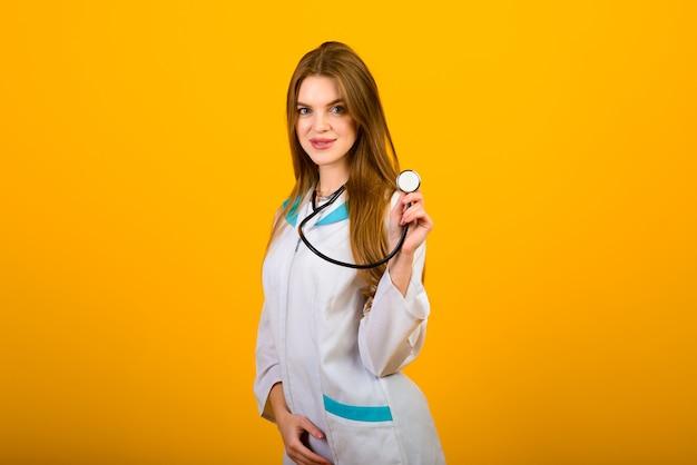 Porträt der ärztin mit stethoskop, das kamera auf gelb betrachtet