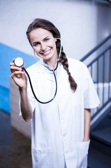 Porträt der ärztin stethoskop im krankenhaus zeigend