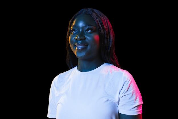 Porträt der afrikanischen jungen frau auf dunkler wand im neonkonzept des gesichtsausdrucks der jugendverkaufsanzeige des menschlichen gefühls