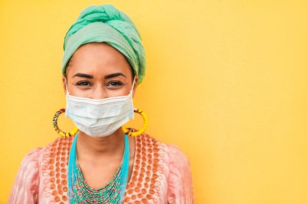 Porträt der afrikanischen jungen frau, die gesichtsschutzmaske trägt - glückliche frau, die böhmische kleidung während des ausbruchs des coronavirus trägt - ethnischer und covid19 lebensstil