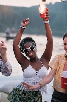 Porträt der afrikanischen jungen frau in der sonnenbrille, die bier trinkt und während der party im freien tanzt