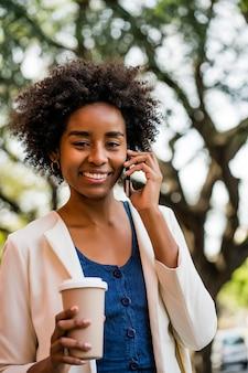 Porträt der afro-geschäftsfrau, die am telefon spricht und eine tasse kaffee hält, während sie draußen im park steht