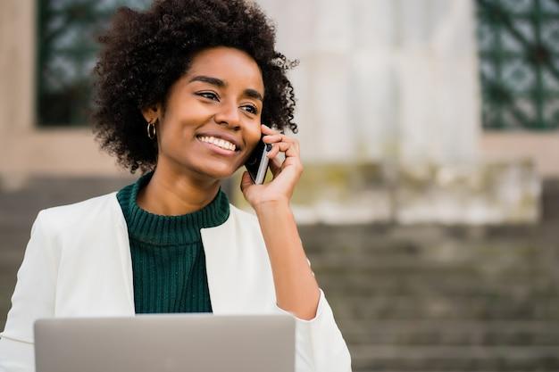 Porträt der afro-geschäftsfrau, die am telefon spricht und ihren laptop benutzt, während sie auf treppen draußen sitzt. geschäftskonzept.