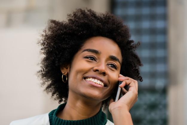 Porträt der afro-geschäftsfrau, die am telefon spricht, während sie draußen an der straße steht. geschäfts- und stadtkonzept.