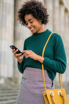 Porträt der afro-geschäftsfrau, die ihr handy benutzt, während sie draußen auf der straße steht. geschäfts- und stadtkonzept.