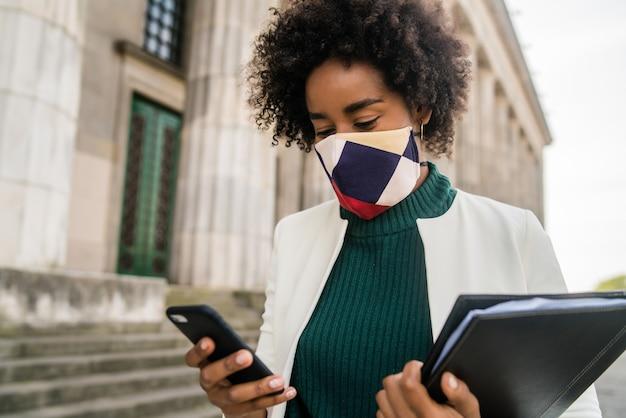 Porträt der afro-geschäftsfrau mit schutzmaske und unter verwendung ihres handys, während draußen an der straße stehend. geschäfts- und stadtkonzept.