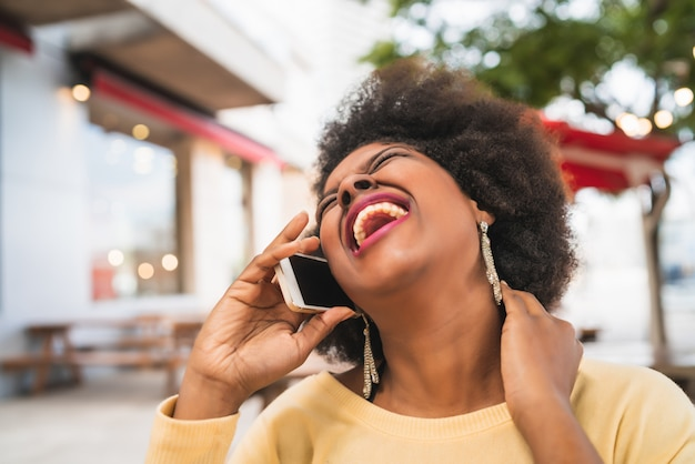 Porträt der afro-lateinamerikanischen frau, die am telefon spricht, während sie am kaffeehaus sitzt. kommunikationskonzept.
