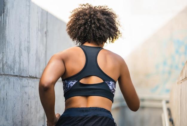 Porträt der afro-sportlerin, die im freien läuft und übung tut