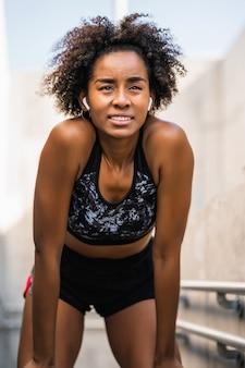 Porträt der afro-sportlerin, die sich nach dem training im freien entspannt