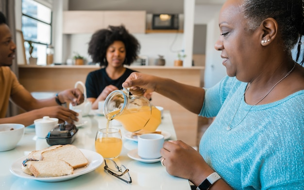Porträt der afroamerikanerfamilie, die zu hause zusammen frühstückt. familien- und lifestyle-konzept.