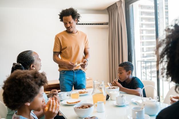 Porträt der afroamerikanerfamilie, die zu hause zusammen frühstückt.