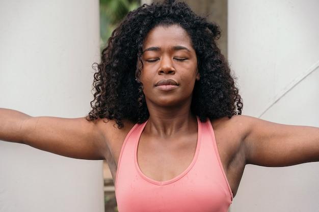 Porträt der afroamerikanerfrau mit geschlossenen augen. horizontale ansicht der fitnessfrau, die sich ausdehnt