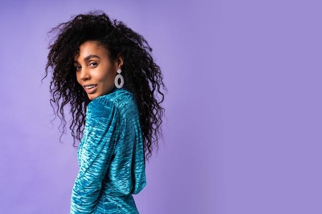 Porträt der afroamerikanerin mit afro-frisur. frau, die festliches kleid des weißen samts trägt.