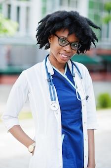 Porträt der afroamerikanischen ärztin mit stethoskop, das laborkittel trägt