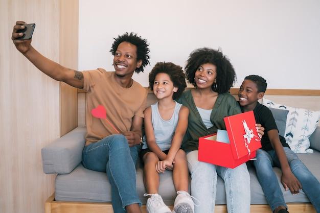 Porträt der afroamerikanischen familie, die ein selfie mit telefon nimmt, während muttertag zu hause feiert. muttertagsfeierkonzept.