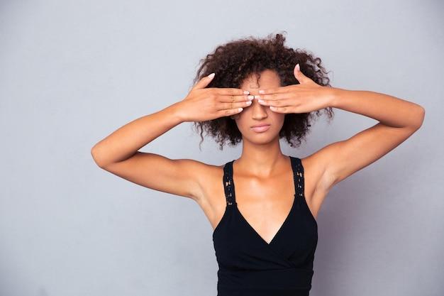 Porträt der afroamerikanischen frau, die ihre augen über graue wand bedeckt