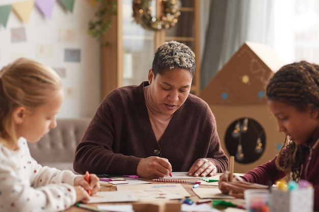 Porträt der afroamerikanischen frau, die kunstklasse mit kindern unterrichtet, die in der schule zeichnen