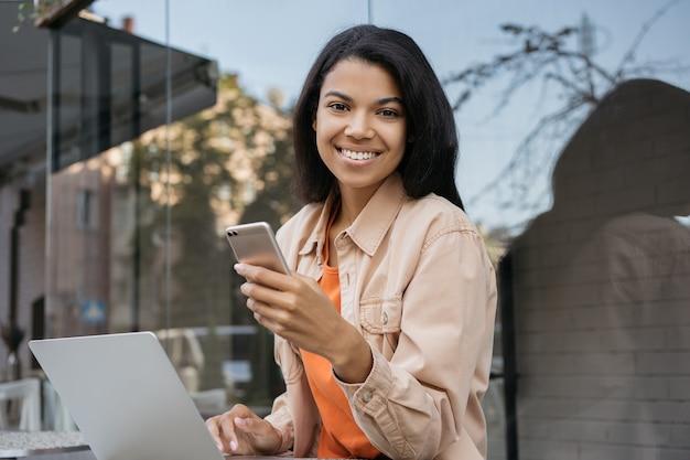 Porträt der afroamerikanischen geschäftsfrau, die laptop-computer, internet, haltendes handy, lächelnd verwendet