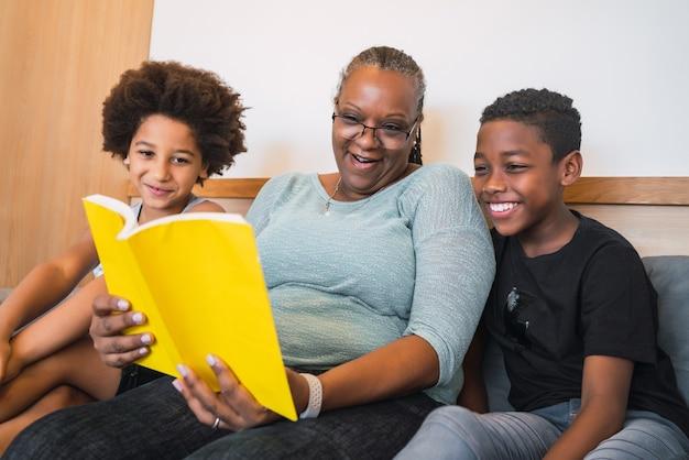 Porträt der afroamerikanischen großmutter, die ihren enkelkindern zu hause ein buch vorliest. familienkonzept.