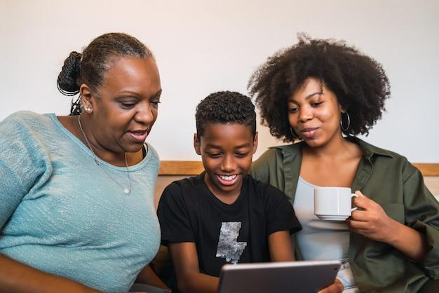 Porträt der afroamerikanischen großmutter, mutter und des sohnes, die ein selfie mit digitalem tablett zu hause nehmen. technologie- und lifestyle-konzept.