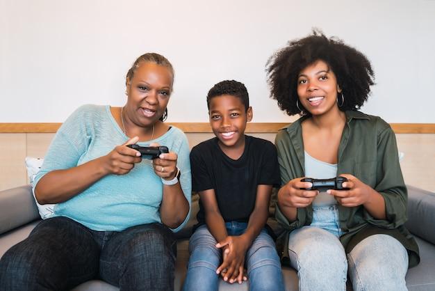 Porträt der afroamerikanischen großmutter, mutter und des sohnes, die zusammen videospiele zu hause spielen. technologie- und lifestyle-konzept.