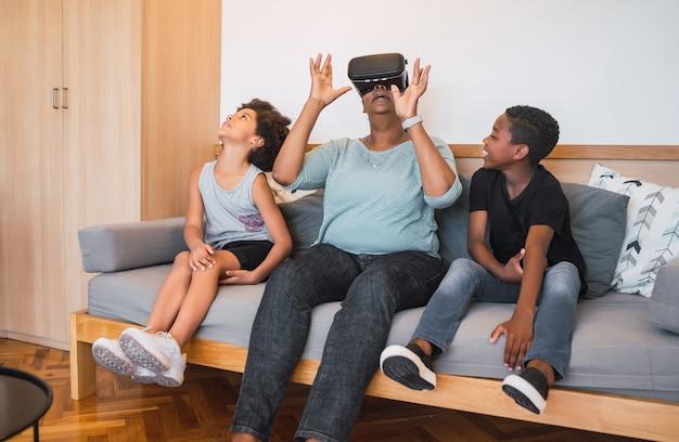 Porträt der afroamerikanischen großmutter und der enkelkinder, die zu hause mit vr-brille zusammen spielen. familien- und technologiekonzept.