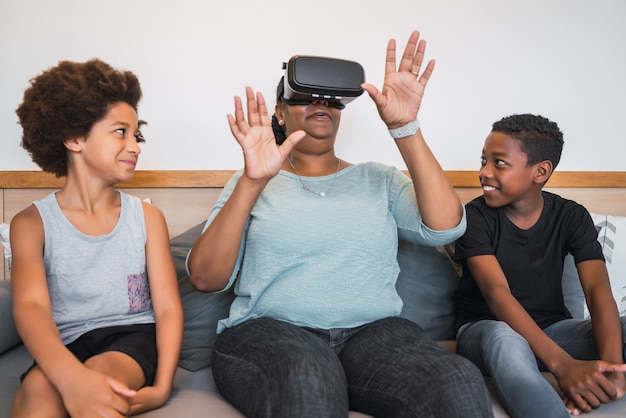 Porträt der afroamerikanischen großmutter und der enkelkinder, die zu hause mit vr-brille zusammen spielen. familien- und technologiekonzept. Premium Fotos