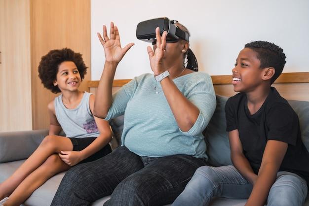 Porträt der afroamerikanischen großmutter und der enkelkinder, die zu hause mit vr-brille zusammen spielen.