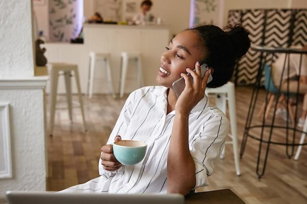 Porträt der angenehm aussehenden jungen frau mit der dunklen haut, die im café sitzt und kaffee trinkt, nette rede auf ihrem handy hat, freizeitkleidung trägt