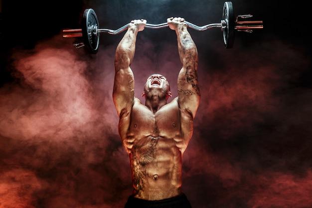 Porträt der anhebenden dummkopf des muskulösen mannes im roten rauch übung für trizeps-motivation