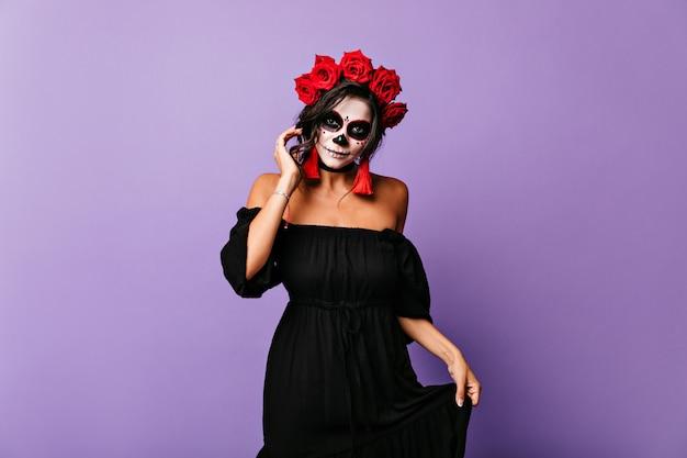 Porträt der anmutigen lateinisch gebräunten frau im halloween-blick. mädchen im schwarzen kleid berührt ihre leuchtend roten ohrringe