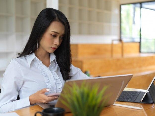 Porträt der arbeiterin, die sich auf ihre arbeit mit laptop im gemeinsamen arbeitsraum konzentriert