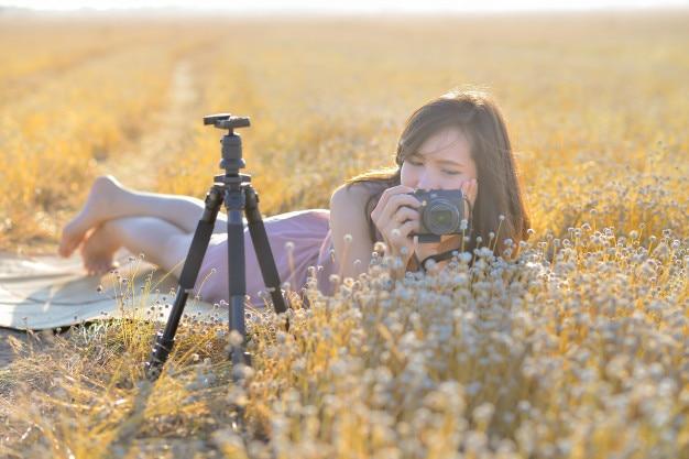 Porträt der asiatin eine kamera auf dem gebiet des trockenen grases halten.