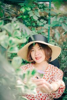 Porträt der asiatin mit hut lächelnd im sommerkaffeestubecaféweinlesefarbton.