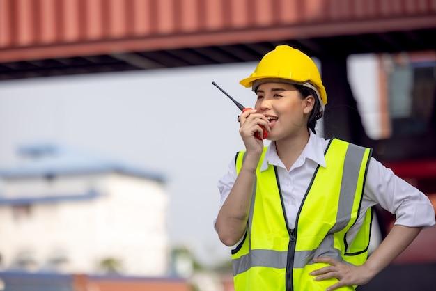 Porträt der asiatischen arbeiterfrau in der sicherheitsuniform, die mit walkie talkie spricht, um arbeitsqualität am containerlager zu kontrollieren. arbeiten für logistik- und versandunternehmen.