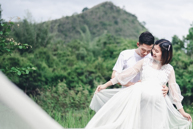 Porträt der asiatischen ehemannumarmung und des küssens seiner schwangeren frau. asiatisches konzept des verheirateten paars und der familie.