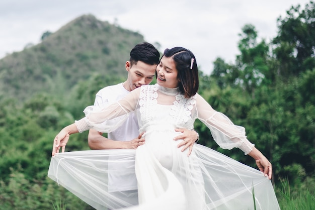 Porträt der asiatischen ehemannumarmung und des küssens seiner schwangeren frau mit natürlichem hintergrund
