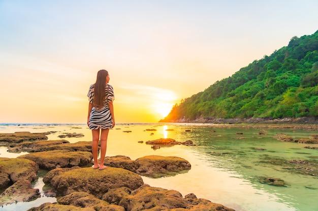Porträt der asiatischen frau auf dem felsen bei sonnenuntergang um ozean im urlaub