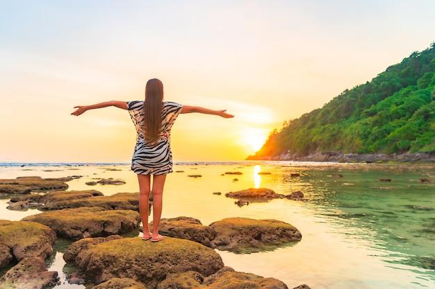 Porträt der asiatischen frau auf dem felsen mit geöffneten armen bei sonnenuntergang um ozean im urlaub