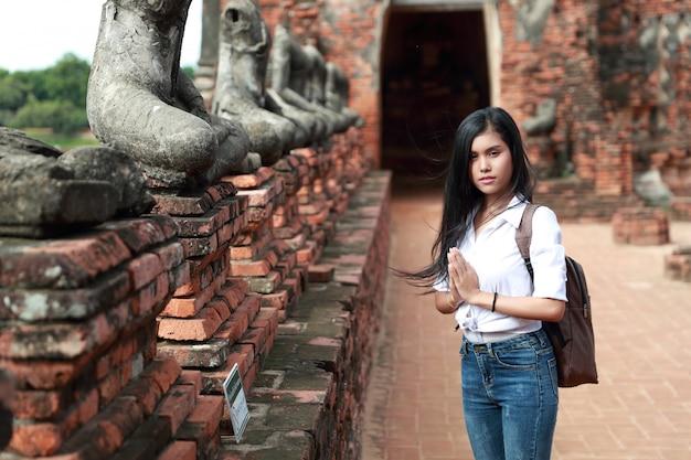 Porträt der asiatischen frau des schönen reisenden, die respekt im alten tempel zahlt